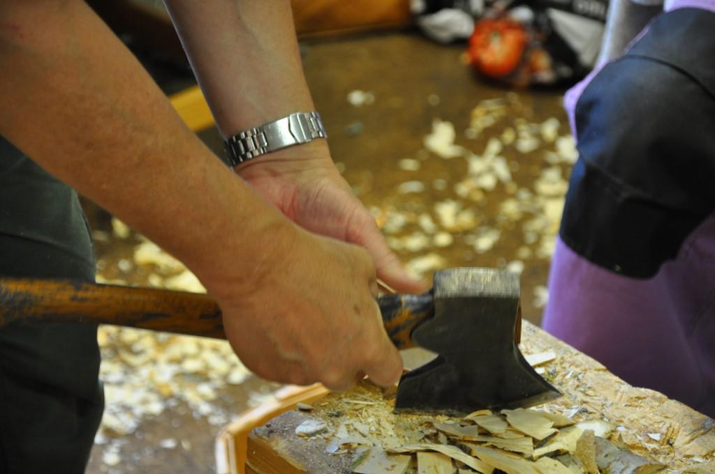 yxa till materialet innan det är dags att tälja. Händer som håller en yxa på en huggkubbe